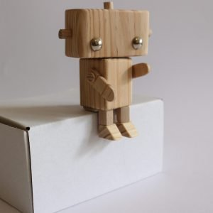 Wooden pine robot, sitting on a white box with a white background. Craft kit for kids and adults form Bot Workshop